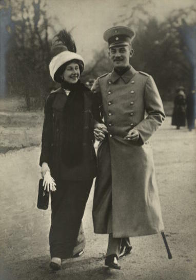 The prince and princess dressed in coats and hats, walking together in a park-like setting while holding hands and smiling.