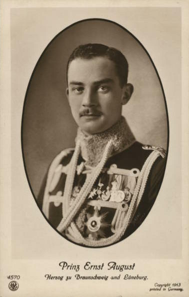 Black and white photo dated 1913 of Prince Ernst August dressed in a military tunic adorned with medals, orders and aiguillettes.