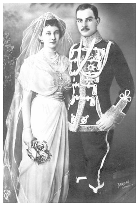 Black and white photo of the princess dressed in white gown, multi-strand pearl necklace, and tiara with veil; and the prince, dressed in military uniform with frogging, aiguillettes, medals and orders on the tunic.