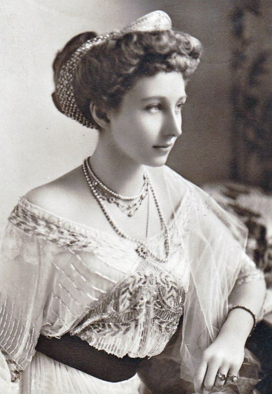 Black and white photo of Princess Viktoria wearing a beaded and embroidered gown, several necklaces and rings.