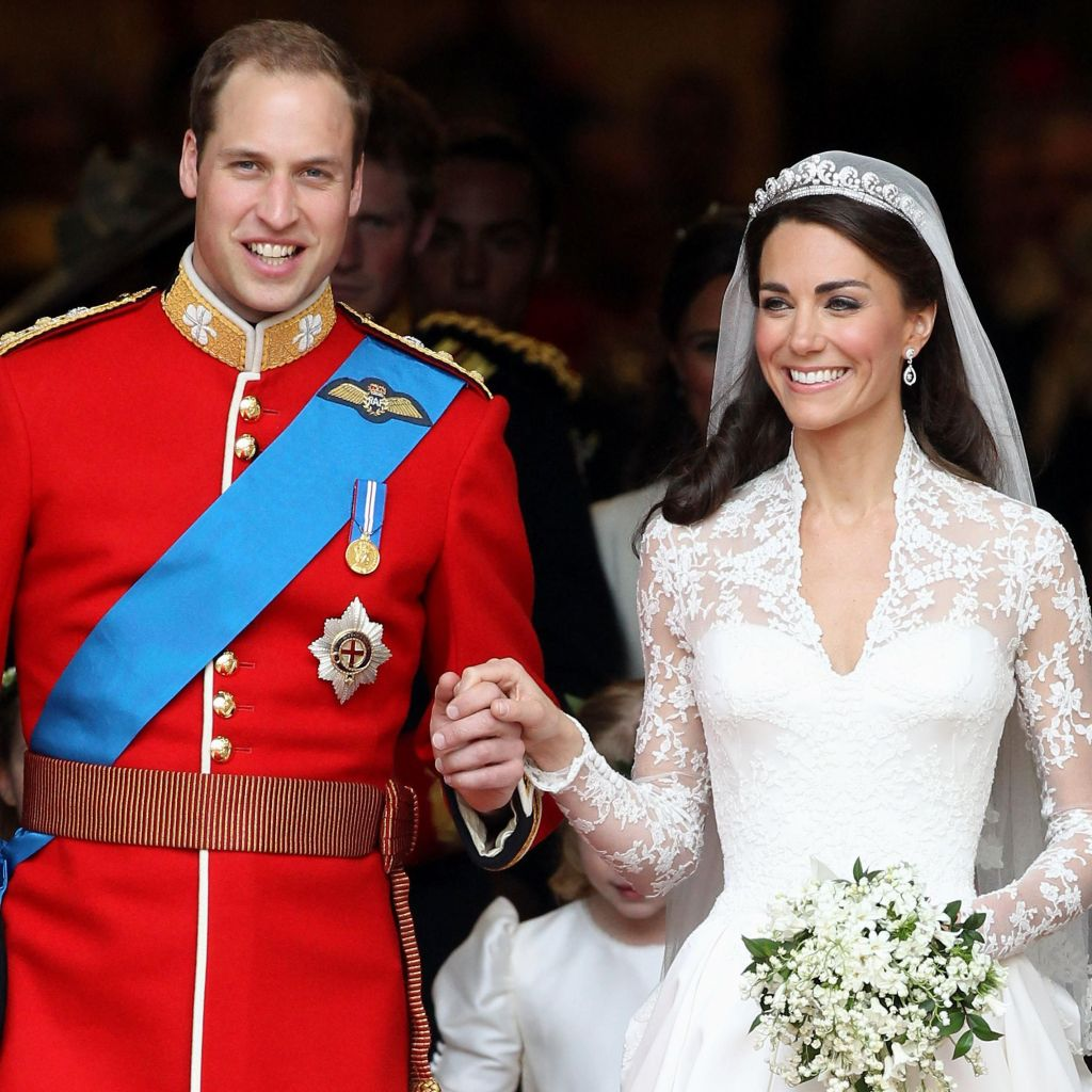 Photo of Prince William, dressed in red army tunic decorated with royal orders and Kate Middleton, dressed in white wedding gown and veil. In one hand she carries a bouquet of white flowers; her other hand is in Prince William's.